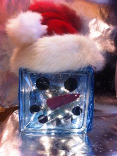 I made this snowman using a glass block and drilling a hole in the bottom to thread in lights. Construction paper was used for his face and some fun blue cello wrap to tie it all together.