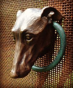 Cast bronze resin Whippet head doorknocker with hand-forged steel ring. All knockers are given a patina and a clear wax UV protective coat. All doorknockers are designed and created by artist, Kerry McGuire. All are signed and numbered. Once the mold is no longer viable, there will be no