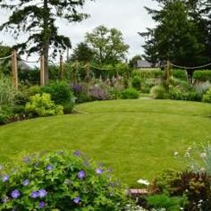 circular lawns and timber posts support ropes on to which roses and clematis will climb - Garden Design Circular Lawns
