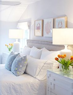 Comfy beach bungalow bedroom boasts a shiplap slanted ceiling framing pale gray walls holding framed beach art beside a window dressed in a white roman shade and over a gray velvet upholstered headboard accented with a silver nailhead trim.