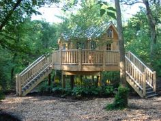 """Located in a natural clearing, it's constructed out of cedar and has reclaimed windows and a standing-seam metal roof. """"The owner wanted the treehouse to look like a quaint cottage in the woods.  It has an L-shaped floor plan with a half-round deck that connects the two legs."""""""
