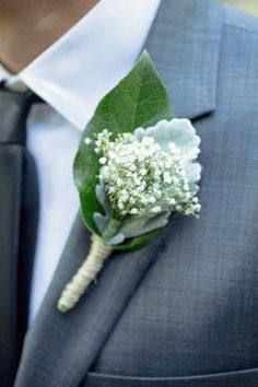 baby's breath/ dusty miller boutonniere on a gray suit.