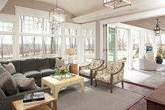 Living room   Taupe walls, white trim, medium wood floor, greenish-grey couches, taupe and yellow accents
