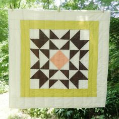 Sadie Patchwork Unisex Baby Quilt. A cotton fabric with  cotton quilting floss, handmade in Asheville, North Carolina, that can be used as a baby quilt, throw blanket, or beautiful wall hanging. You can choose from 17 different colors of these geometric patterns to make yours unique. A great baby shower gift.