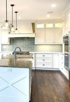 Three glass pendants hang over a white kitchen island topped with gray granite fitted with a farmhouse sink and satin nickel gooseneck faucet. Kitchen with white cabinets paired with white granite countertops and a gray subway tiled backsplash. A white beadboard kitchen hood stands over an integrated gas cooktop with pot and pan drawers below.