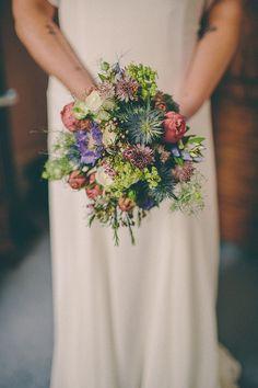 Buquê de noiva colorido, em tons de verde, roxo e laranja.