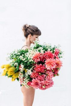 woman standing behind bright flowers via photographer luisa brimble / sfgirlbybay