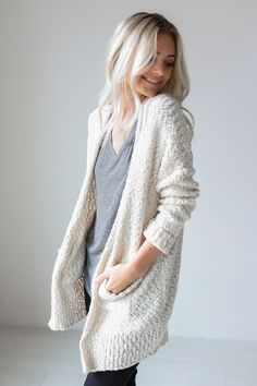 """• Cream thick knitted cardigan with pockets • Available in S/M and M/L. Model is 5' 4"""" and wearing a size S/M • 55% Cotton, 45% Acrylic"""