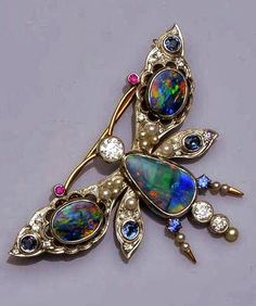 Opal Butterfly Brooch - A vari gem-set butterfly brooch - The butterfly with cabochon opal body, brilliant-cut diamond head and tail, and circular-cut ruby antennae, the outspread wings with pierced detail, set with opal doublets, mixed-cut sapphires, single-cut diamonds and small cultured pearl highlights, wing span 6.6cm.