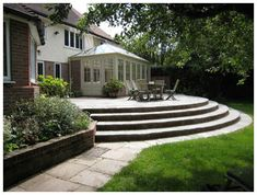 A large raised patio designed to give easy access from kitchen, dining room and conservatory and plenty of room for outdoor dining and leisure activities. Sweeping steps provide easy access to the lawn. A rear garden design in Hertfordshire. Patio Steps, Garden Steps, Concrete Patios, Cozy Patio, Backyard Patio, Small Outdoor Patios, Outdoor Dining, Small Patio Design, Bohemian Patio