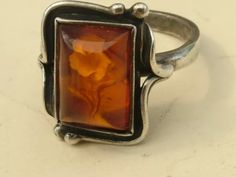 A carved intaglio amber and Sterling Silver ring.