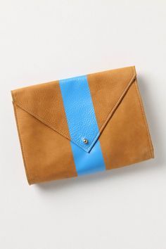 This clutch is absolutely striking in person. Soft and supple natural leather with leather lining, silkscreened bold slue stripe and a sleek brass enclosure.     Totally lusting after this one.