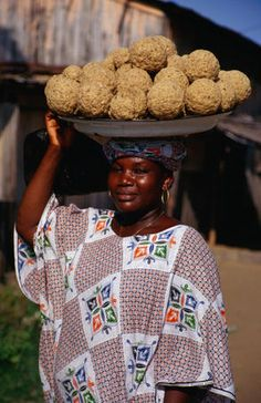 Woman with a pan full of sea sponges on her head, Ivory Coast, Africa