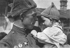A Czech baby plays with the decorations of a Soviet soldier in Prague in 1945. The baby is wearing a traditional Czech dress. Soviet propaganda was particularly fond of such photos.