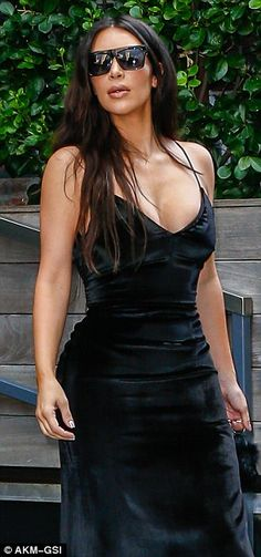 Flaunting it: Kim wore a skintight floor length velvet black dress that showed off her famous curves