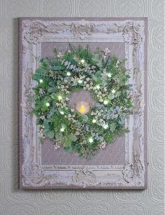 Painted ornate frame with chicken wire over mirror & lighted wreath with candle.