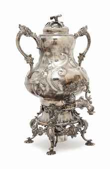 A silver hot water urn. It is the idea of a lifestyle enabling the enjoyment of pouring enough cups of tea to actually make this item feel useful.