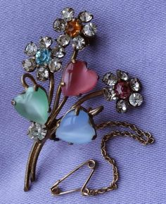 This exquisite brooch has a wonderful flowers & hearts design. It is adorned with gorgeous adularescent pink, green & blue heart-shaped glass cabochons, plus faceted amber, blue, pink & clear glass stones.