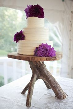 simple cake accented with purple flowers & perhaps the best rustic cake stand ever