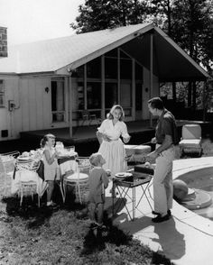 1950s family grilling hamburgers beside pool in backyard cookout.