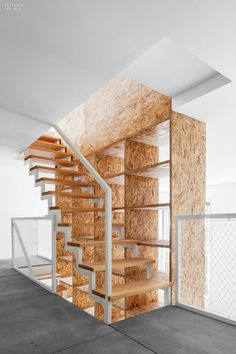 The Art of Storage: Domingos Lopes' Porto House | OSB built-ins rise through the center of the house. #interiordesign #design #interiordesignmagazine #products #storage #dramaticstaircases