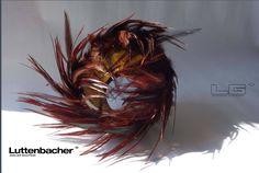 """Geraldine Luttenbacher - Bracelet en noix de coco - deux noix de coco ajustées l'une et l'autre forment la partie """"solide"""" de la pièce,   assemblées par des rivets en Or9carat   - L'intérieur des bracelets est   doré à la feuille d'or24ct  - les plumes sont cousues et assemblées entre les deux parties en noix de coco. - bracelets réalisés en 2014"""