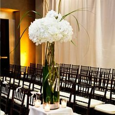 Tall cylinders filled with white hydrangeas and curly willow topped each column.