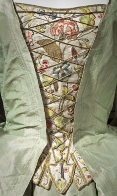 Detail of a stomacher – robe a la Française – c.1725. Bright green silk taffeta, stomacher embroidered with flowers in coloured silk and metal thread.