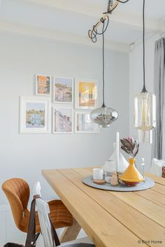 Interior oak table, house doctor lamps, grey wall with photoframes ©BintiHome