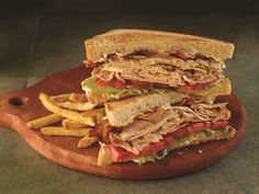 It's the Classic Club Sandwich!    Toasted sourdough bread layered with a rich mayonnaise, iceberg lettuce, vine-ripened tomato, smoked bacon and thinly sliced grilled chicken.