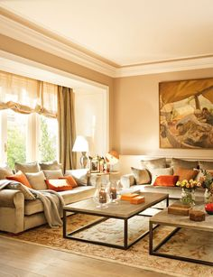 Warm & transitional living room in neutrals with orange accents
