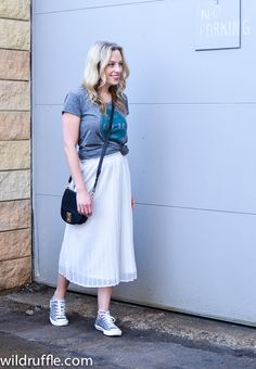 Pleated midi skirt with a casual tee, cross body bag, and Chuck Taylors
