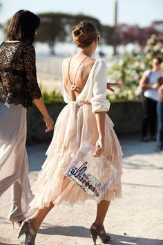 Open back blouse with a hanging necklace and blush tulle skirt
