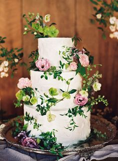 These vanilla buttercream-topped layers concealed raspberry-lemon, chocolate-mocha, and carrot cake tiers, but the real highlight of this gorgeous cake are its wild and whimsical floral accents. The assortment of blush flowers and delicate vines is nothing short of picture perfect.