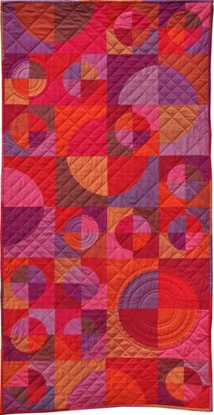 """Ruby Reds in Circles and Crescents""  quilt by Jutta and Anka of quilt-around-the-world.com.  Drunkard's Path blocks, Oakshott Cottons, pattern available."