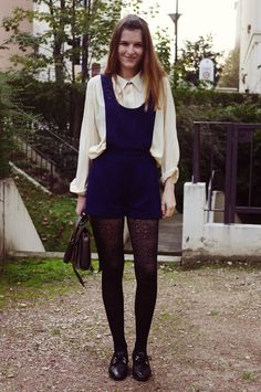 Lady Moriarty. Navy pinafore on cream blouse and black patterned tights.