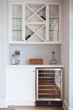 A clean and organized dry bar is a great option for a small nook. Here, a wine refrigerator and cabinet create the base of the bar. Above, built-in shelving and glass-front cabinets provide wine bottle and glass storage.
