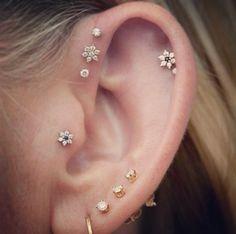Um ~*~piercing de constelação~*~ consiste em uma coleção de pequenos brincos dispostos como estrelas nas orelhas.
