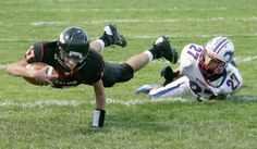 Dalton sophomore Zach Ryder holds tight to the football following a tackle by Tuslaw senior Dion Perez.