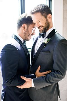Same sex wedding at the 1912 groom grey tuxedo with white dress shirt and grey and black stripped bow tie with white floral boutonniere with groom navy blue tuxedo with white dress shirt and black bow tie and white floral boutonniere