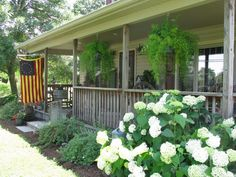 This would be my perfect porch because of the Annabelle hydrangea and the hanging asparagus ferns! Also, the slightly faded American flag adds a primitive touch for my taste!!