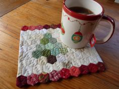 Christmas Tree Mug Rug: Here's a quick and portable little project for you English paper piecing lovers. The only *challenge* here is the size of these little hexies. Which only makes this little mug rug really, really cute!
