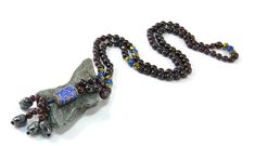This mala necklace is crafted with 108 semi precious stones of granada surrounded by gold hematite &