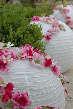 Idée déco : pour encadrer un chemin de mariés, des lampions décorés avec quelques fleurs