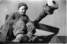 "A young Russian orphan poses for the camera atop a disabled German anti-tank gun. He is wearing clothing he either lifted from Russian KIAs or received from some empathetic Russian soldier. ""Front orphans"" were a routine fixture during the war on the Eastern Front -- children who had lost both parents and left to their own devices; some were ""adopted"" by military units and tied to survive as best as they could."