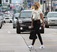 Off-duty chic: The fashion It girl bared her toned midriff in a white crop top and high-waisted leggings that featured zipper detailing near her hips
