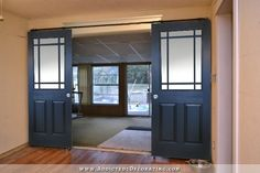 Black rolling barn door style doors with nine panes of glass of unequal size on top
