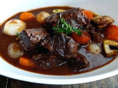 Beef Bourguignon  This is a rustic peasant dish hailing from the Bourgogne countryside, featuring the region's red wine. Beef slow-cooks in red wine until it's falling-apart tender, while its juices blend with the wine and vegetables for a rich, flavorful stew.