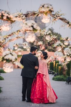 Candid Couple Shot - Bride in a Fuchsia Pink and a Light Pink Cape and the Groom in a Black Suit | WedMeGood #wedmegood #indianbride #indiangroom #decor #fairylights #candidcoupleshot #indianwedding #gown