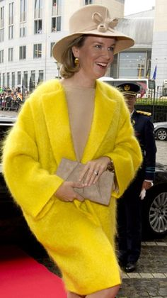 Queen Mathilde of Belgium in a Tan with yellow dress over yellow angora coat with a matching decorative hat and clutch during visit in the city of Liege, 11.10.13
